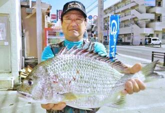 西原海岸で48・2センチ、1・85キロのチンシラーを釣った亀谷長治さん=14日