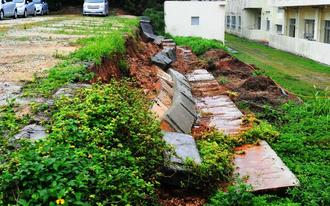 豪雨の影響で、隣の久米島西中学校敷地内へ崩れ落ちたレンタカー駐車場の塀=4日、久米島町西銘(比嘉正明通信員撮影)