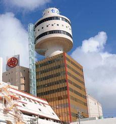 売却が決まった那覇タワー。後方に見えるのは沖縄三越=那覇市牧志