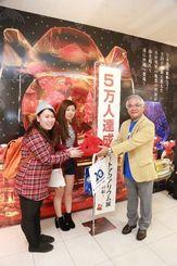 琉球朝日放送の上原常務から記念品を受け取る石川さん(左)と上原さん(中央)=17日、那覇市のデパートリウボウ