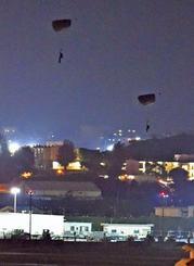 米軍嘉手納基地で夜間にパラシュートで降下する米兵=10日午後8時3分、嘉手納町役場から(金城健太撮影)
