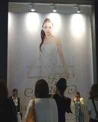 安室奈美恵さんの展覧会の幕の前で記念撮影するファンたち=大阪市