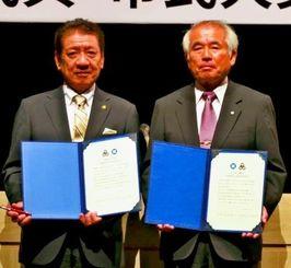 兄弟都市40周年記念で共同宣言文に署名した桑江朝千夫市長(左)と豊中市の淺利敬一郎市長=8日、ミュージックタウン音市場
