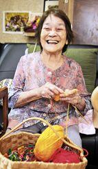自宅で編み物をしながら笑顔を浮かべる宮城スミ子さん=11月19日、南城市大里仲間