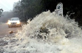 大雨で排水溝からあふれ出る雨水で冠水した道路=25日午後3時50分、国頭村安田