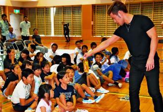 MASAマジックさんがカードとペットボトルを使ったマジックに目を輝かせる児童=2日、竹富小中学校