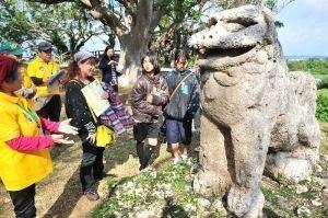 富盛の石彫大獅子を見学するバスツアー参加者たち=八重瀬町富盛