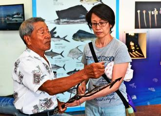 突きん棒漁に使うモリを手にする張旺仔さん。右は酒井充子監督=1日、台湾・台東県成功鎮