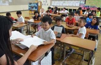 担任の多田弘枝先生から「あわせっ子のあゆみ」を手渡され、笑顔を見せる子どもたち=5日午前、沖縄市・泡瀬小学校