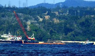 オレンジ色のフロート(浮具)が付いた汚濁防止膜を海上に引き出す作業船=9日午前11時2分、名護市辺野古沖(山田優介撮影)