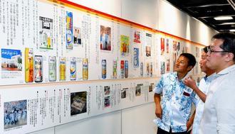オリオンビール60年の歴史を振り返る展示に見入る来場者=11日午後、那覇市久茂地・タイムスギャラリー
