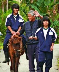 ポニー乗馬と手綱を引く職場体験をした羽地中の大兼久さん(右)仲村渠さん(左)=18日、名護市・ネオパークオキナワ