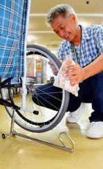「手であが~る」で車いすを持ち上げ、車輪を拭く落合さん=石垣市役所