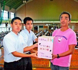 北中城中学校の生徒から募金を受け取る桃原英樹・のあちゃんを救う会事務局長(右)=北中城中学校