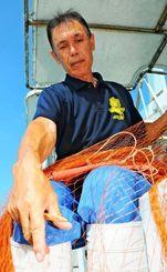 亡くなった先輩漁師から受け継ぐ網を手入れする樋岡邦彦さん。愛着深い港川の象徴・トビウオ漁を続ける