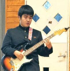 生徒会主催のイベントでエレキギターを弾く與儀浩志さん。「楽しんで弾けて良かった」=1月22日、那覇市・寄宮中学校体育館