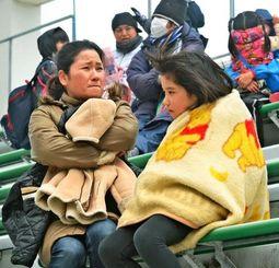 毛布などに身を包み完全防備でサッカー観戦を楽しむ家族連れ=24日午後1時25分、国頭村陸上競技場