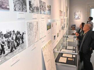 企画展「ウチナーンチュが見た戦前・戦時下の台湾・フィリピン」の展示物を見学する来館者=9日、糸満市摩文仁・県平和祈念資料館