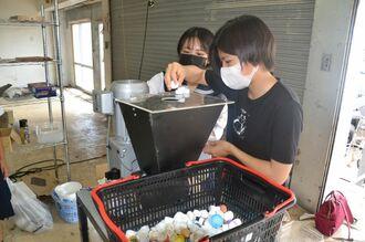石垣島の海岸に漂着していたペットボトルのふたを粉砕機に入れるメンバーの奥濵寿虹さん(右)ら=18日、石垣市内