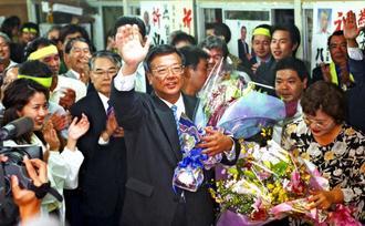 那覇市長選で当選を確実にし、支持者から贈られた花束を手に笑顔を見せる翁長氏(中央)=2000年11月12日、那覇市天久