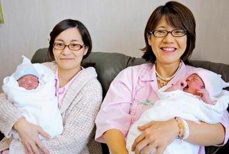元日に生まれたわが子を抱く屋良郁乃さん(左)と宮平恵実さん=1日、那覇市首里汀良町の伊波レディースクリニック