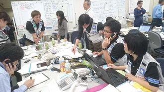 熊本県職員と連携する琉球病院先遣隊チームの白いジャケットを着た(右から)野村れいかさん、知花浩也さん、福田貴博さん、伊波芳暁さん=15日午後7時30分ごろ、熊本県庁(琉球病院提供)