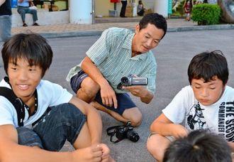 ティーダキッズプロジェクトで伊江島を訪れた子どもたちを撮影する坂田竜二さん(中央)=2012年8月、伊江村内