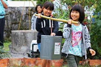 地下ダムの井戸からくみ上げた水を2人一組で運ぶ児童ら=伊是名村伊是名