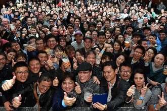 酒場詩人・吉田類さん(中央手前)を囲み乾杯する来場者=16日、沖縄市コザミュージックタウン音市場