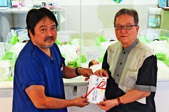 武富和彦社長(右)に100万円を寄付する上村哲院長=5日、中城村・うえむら病院