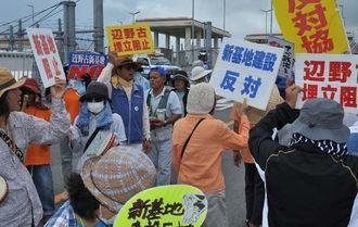 プラカードを手にデモ行進をする辺野古新基地建設に反対する市民ら=14日午前、名護市のキャンプ・シュワブゲート前
