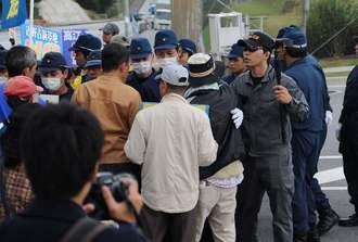 ゲート前で抗議する市民らを歩道へ押しやる機動隊=10日午後3時すぎ、名護市辺野古のキャンプ・シュワブゲート前