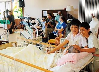 ホスピス・コンサートで「時間よ止まれ」のリクエスト曲が流れ、ボランティアらと喜びを共有する患者(手前)ら=29日午後、西原町・アドベンチストメディカルセンター