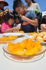 マンゴーの里宣言8周年のイベントでマンゴーをほおばる子どもたち(JAおきなわ提供)