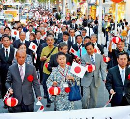 国際通りを歩く「天皇陛下、皇后陛下奉迎提灯大パレード」の参加者=27日午後6時45分、那覇市