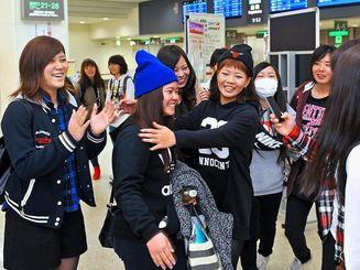 進学で福岡へ旅立つ友人(手前左から2人目)を笑顔で見送る同級生たち=23日午前、那覇空港