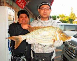 恩納村海岸で70センチ、4.27キロのタマンを釣った藤岡隆司さん(右)=2016年12月31日