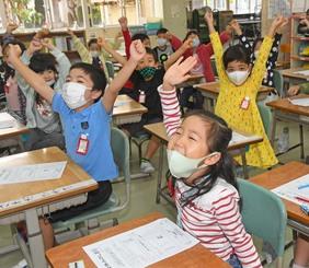 「冬休み何して遊ぶかな?」担任教師の問いかけに元気よく手を上げる金城小学校1年の児童たち=25日午前8時50分、那覇市の同校