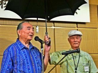同級生から日傘を贈られ、喜びを語る渡口彦邦さん(左)=12日、那覇市・パシフィックホテル沖縄