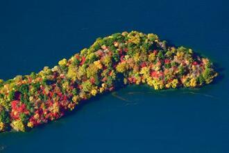 見頃を迎え、中禅寺湖に映える紅葉=24日午後、栃木県日光市(共同通信社ヘリから)