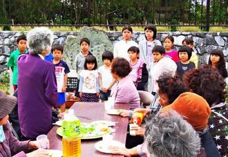 慰霊碑の前で戦争体験者の話を聞く子どもたち=6日、大宜味村喜如嘉・農村環境改善センター