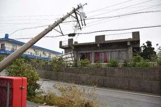 強風で電柱が倒れ、向かいのスナックは飛んできたトタン屋根が窓ガラスを破損した=17日午後3時48分、与那国町久部良集落(山田優介撮影)