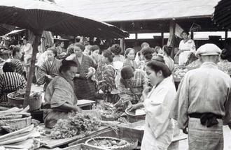 朝日新聞大阪本社で見つかった現在の那覇市東町にあった「那覇ウフマチ(大市)」と呼ばれた市場の写真。立ち並ぶ建物の中に店を設けて品物を売るほか、路上で商品を並べて露店販売をする人々もおり、庶民の生活の場としてにぎわった。市場では品物ごとに販売場所が分かれており、魚・肉・米・乾物等を販売する区域や、野菜・芋・雑貨を売る店舗などがあった=1935年(朝日新聞社提供)
