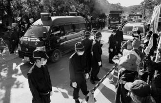 ヘリパッド建設に市民が抗議する中、警察車両の先導で、米軍北部訓練場に入る砂利を積んだダンプカー=11月25日、東村高江