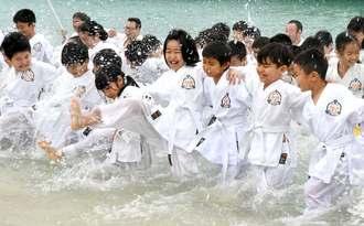 水しぶきを上げ、空手の稽古に励む子どもたち=5日、那覇市若狭・波の上ビーチ(田嶋正雄撮影)