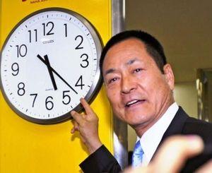 航空機のトラブルで約3時間遅れで那覇空港に到着し、時計を指さすDeNA・中畑監督