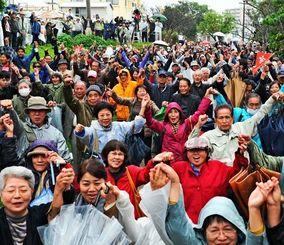 第2回口頭弁論を前にガンバロー三唱で気勢を上げる集会参加者=8日午後、那覇市楚辺・城岳公園
