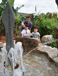新設された噴水で遊ぶ親子=2日、名護市為又・沖縄フルーツランド