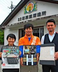 村の特産品が詰められたお歳暮をPRする宮城部長(中央)=11日、大宜味村田嘉里の田嘉里酒造所