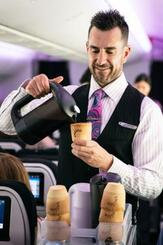 食べられるカップでコーヒーを提供する客室乗務員(ニュージーランド航空提供・共同)
